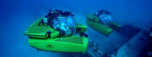 A pair of Triton 3300/3 MKII submersibles explore a shipwreck at Binimi