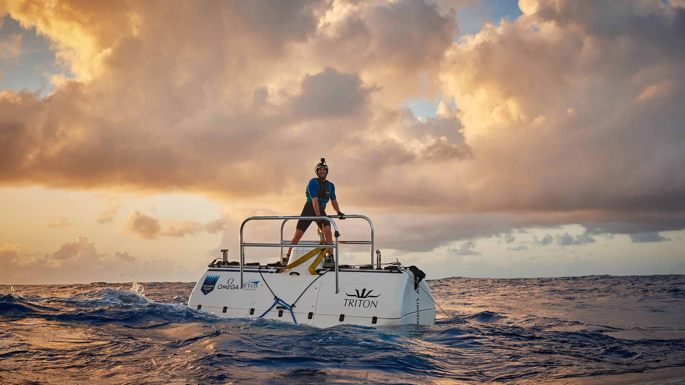 Triton employee Tim on top of the Triton 33000/2 as she dives in the sunset. Reeve Jolliffe.