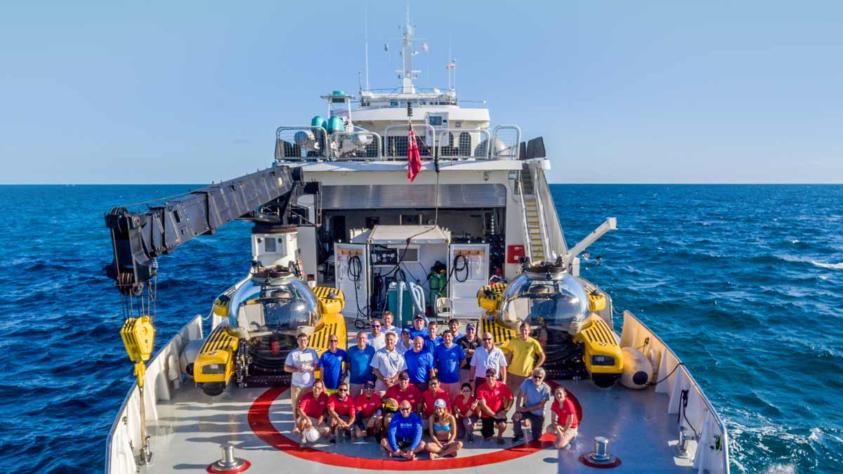 Team Triton pictured on back deck of vessel with two Triton subs in background