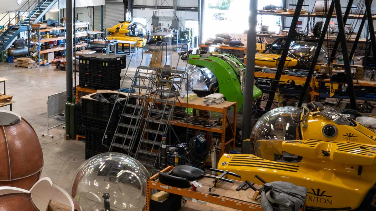 Triton's workshop in Florida, featuring own-brand subs in build and third-party subs undergoing upgrades.